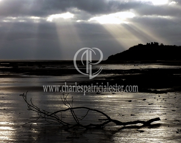 Dramatic bands of sunlight over Llansteffan beach and castle